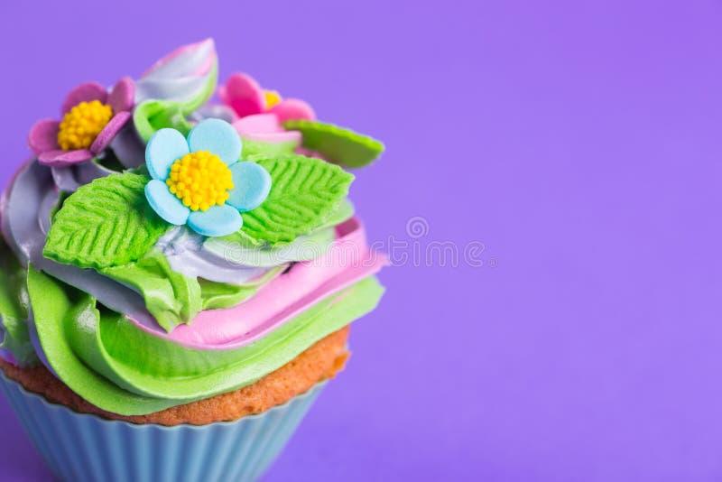 Parte superior colorido cremosa do queque do close up decorada com flores e as folhas coloridas no fundo roxo imagem de stock royalty free