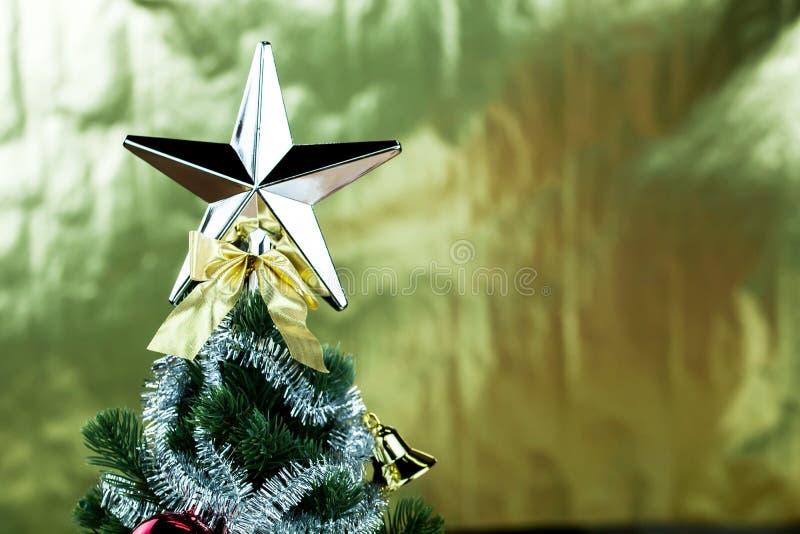 A parte superior da árvore de Natal decorada com protagoniza no fundo brilhante dourado brilhante imagem de stock