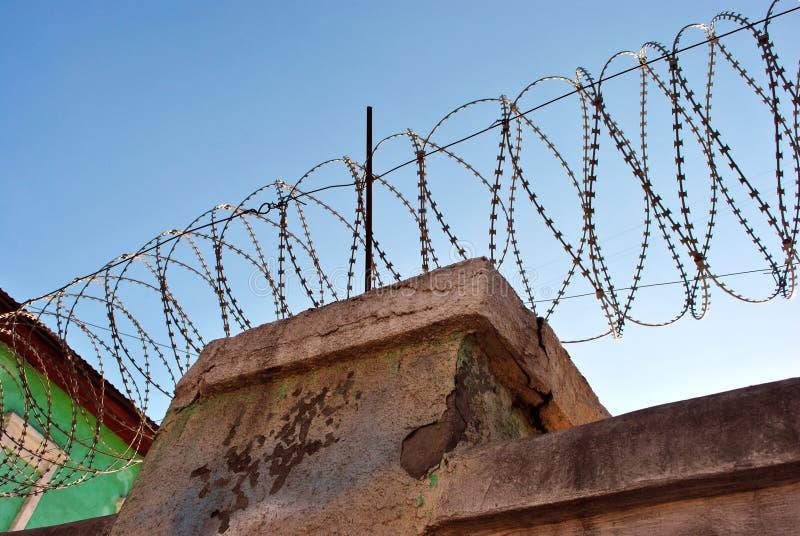 Parte superior da cerca da cadeia com arame farpado, fundo brilhante do céu do inverno foto de stock