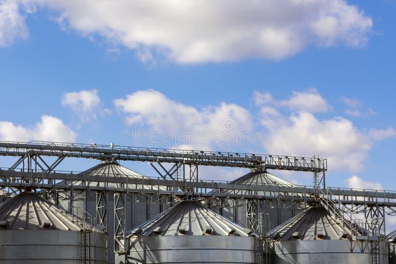 A parte superior das estruturas do metal do elevador de grão no fundo do céu imagem de stock royalty free