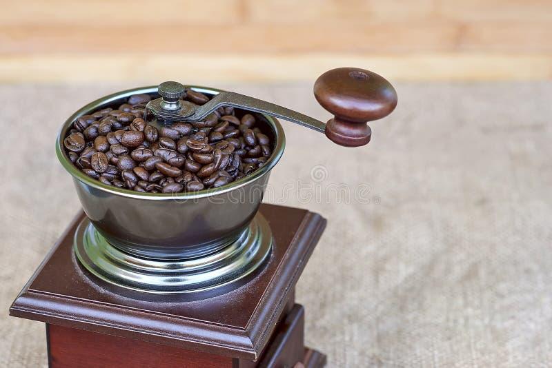 Parte superior de la amoladora de café por completo de los granos de café asados imagenes de archivo