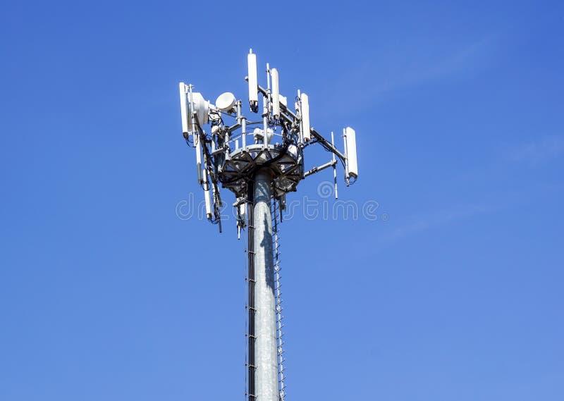 Parte superior de la torre de comunicación del teléfono celular con las antenas múltiples contra un cielo azul fotos de archivo