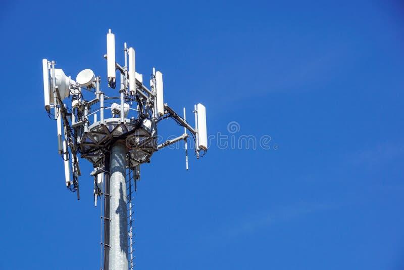 Parte superior de la torre de comunicación del teléfono celular con las antenas múltiples contra un cielo azul fotografía de archivo