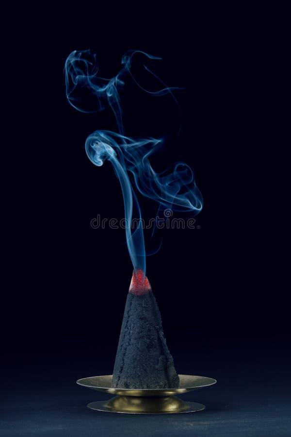 Parte superior de mudanza del humo azul de la forma de cono ardiente del incienso imágenes de archivo libres de regalías