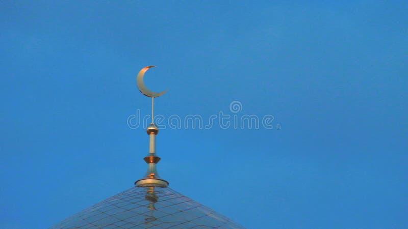A parte superior do minarete dourado da mesquita com um crescente é um símbolo do Islã contra um céu azul com nuvens Esquerda no  fotos de stock