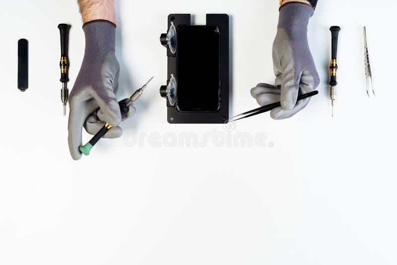 Parte superior quebrada da exposição do telefone esperto do reparo da mão do homem fotografia de stock