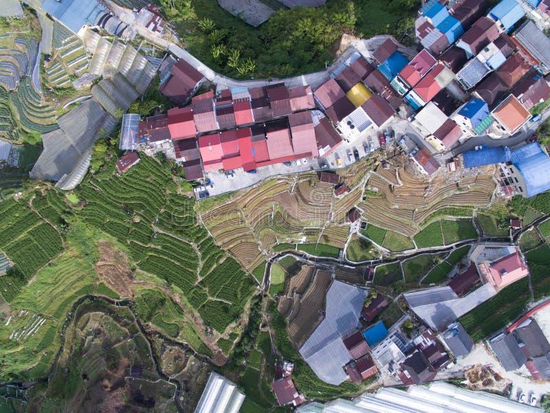 Parte superior a?rea abaixo da vista de uma terra e de casas fotografia de stock royalty free