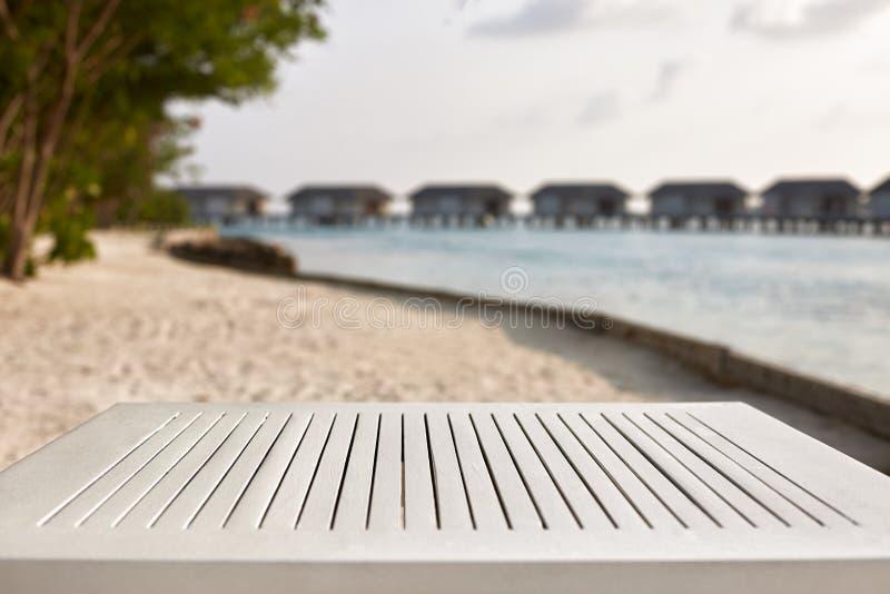 Parte superior vazia da tabela de madeira branca para a colocação e a exposição do produto Lagoa azul com bungalows da água e as  fotos de stock royalty free