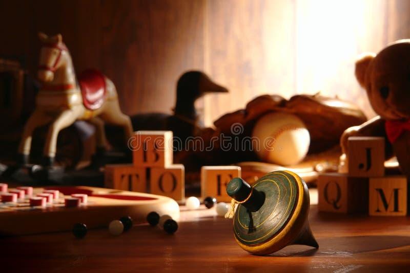 Parte superiore di filatura di legno antica e vecchi giocattoli in soffitta immagine stock libera da diritti