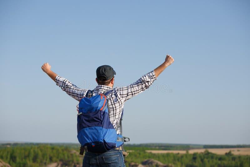 Parte traseira da foto do homem do turista com trouxa, mãos acima no monte no fundo de extensões da montanha, céu azul fotografia de stock royalty free