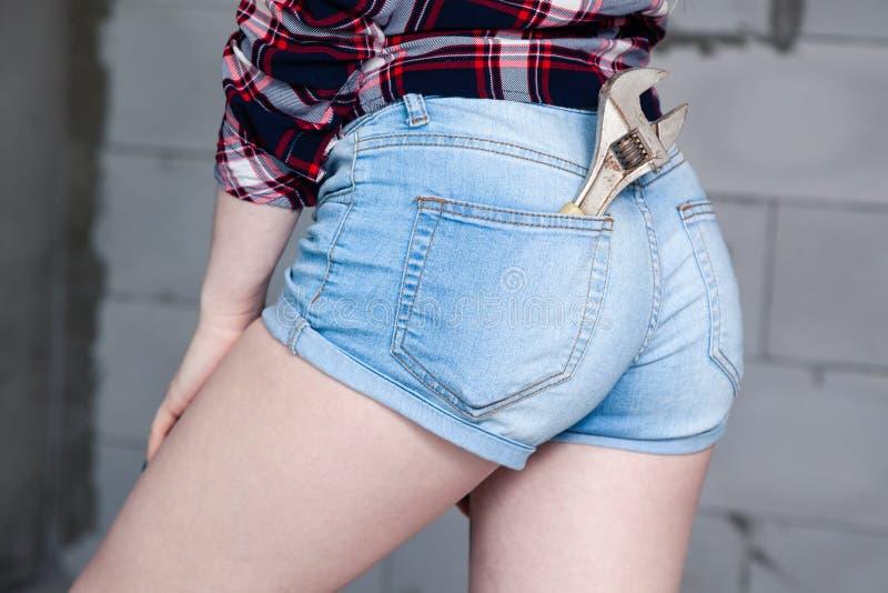 A parte traseira da menina do close up, chave no bolso de macacões azuis das calças de brim da sarja de Nimes, camisa quadriculad imagem de stock royalty free