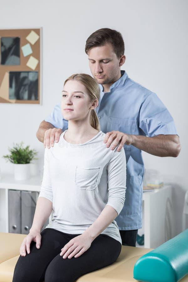 A parte traseira da mulher de exame do fisioterapeuta foto de stock