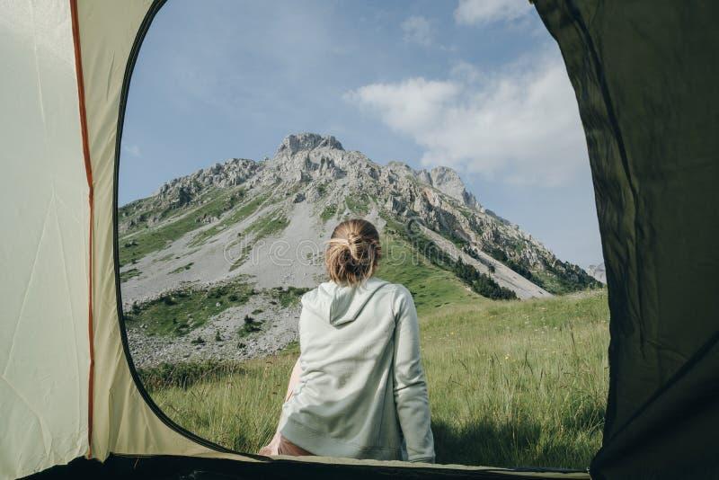 Parte traseira da mulher na barraca com Mountain View em Montenegro, enjo do campista imagens de stock royalty free
