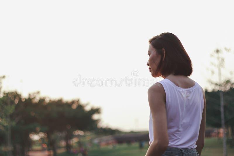 A parte traseira da posição da mulher no por do sol fotos de stock