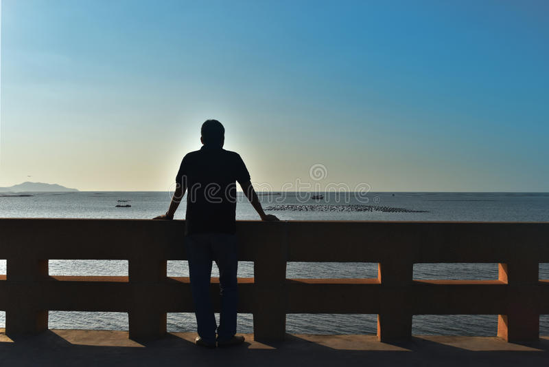 A parte traseira da sombra do homem de Ásia 40 anos velho a parte dianteira é o mar foto de stock