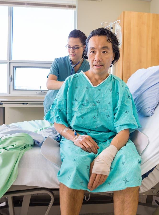 A parte traseira de Examining Patient da enfermeira com estetoscópio sobre foto de stock