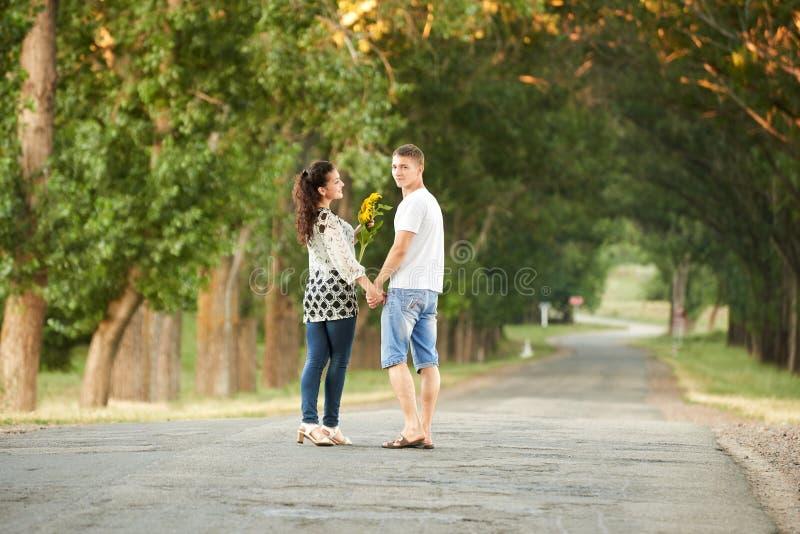 A parte traseira de pares novos anda na estrada secundária exterior, conceito romântico dos povos, temporada de verão imagens de stock royalty free