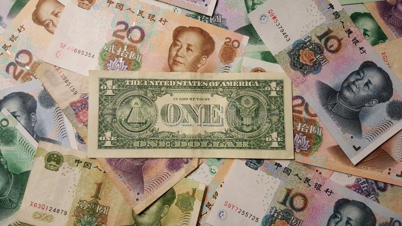 Parte traseira de um dólar americano entre o chinês Yuan Renminbi Banknotes imagem de stock