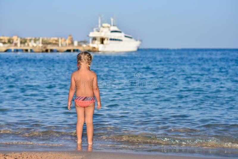 A parte traseira de uma menina em um maiô na praia, um iate no mar fotos de stock