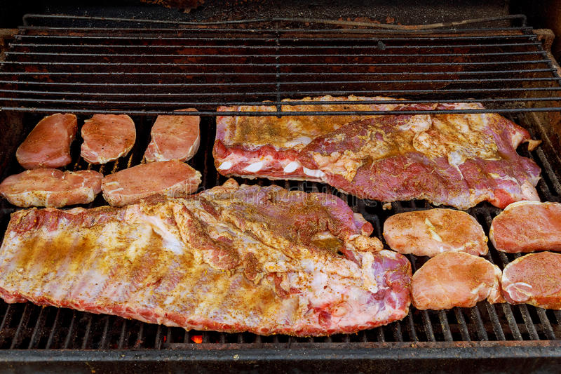 Parte traseira do bebê do BBQ ou close-up dos reforços da costeleta de porco magra na grade flamejante quente imagem de stock