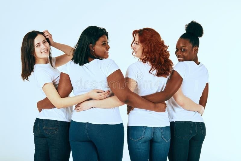 Parte traseira do grupo de ra?a misturada de mulheres na vista ocasional feliz junto no branco imagem de stock