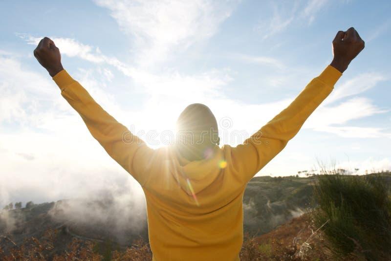Parte traseira do homem afro-americano no hoodie com as mãos levantadas no ar e no sol no fundo foto de stock