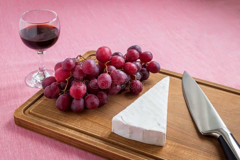 Parte triangular de queijo do brie, de uvas doces vermelhas, de faca do cozinheiro chefe em uma placa de corte de madeira marrom  imagem de stock royalty free