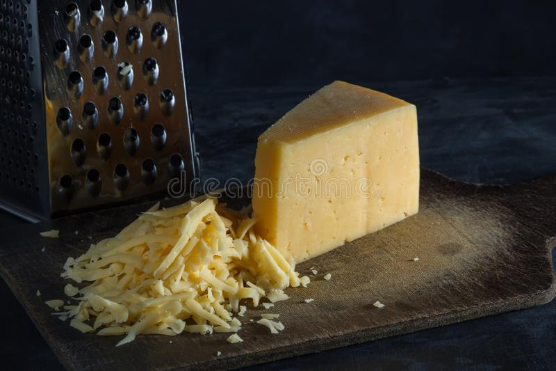Parte triangular de queijo e de queijo raspado em uma placa fotos de stock royalty free