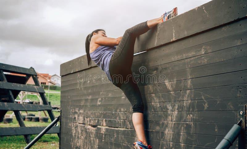 Partecipante alla parete rampicante di corsa ad ostacoli fotografia stock