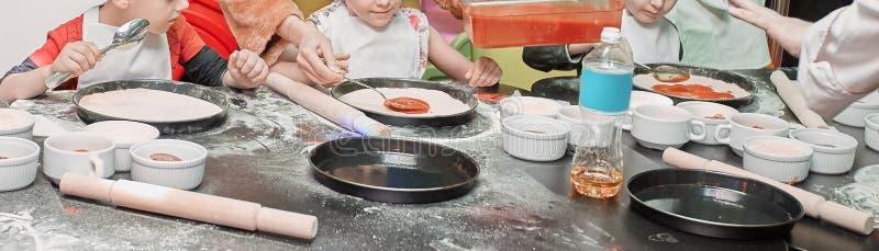 Partecipanti della classe matrice dei bambini che spalma salsa in base alla pizza immagine stock