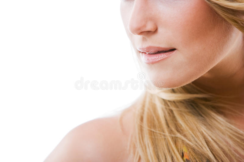 Parted lips of a beautiful woman. Sensual conceptual image of the parted lips and shoulder of a beautiful woman with long blond hair isolated on white stock photo
