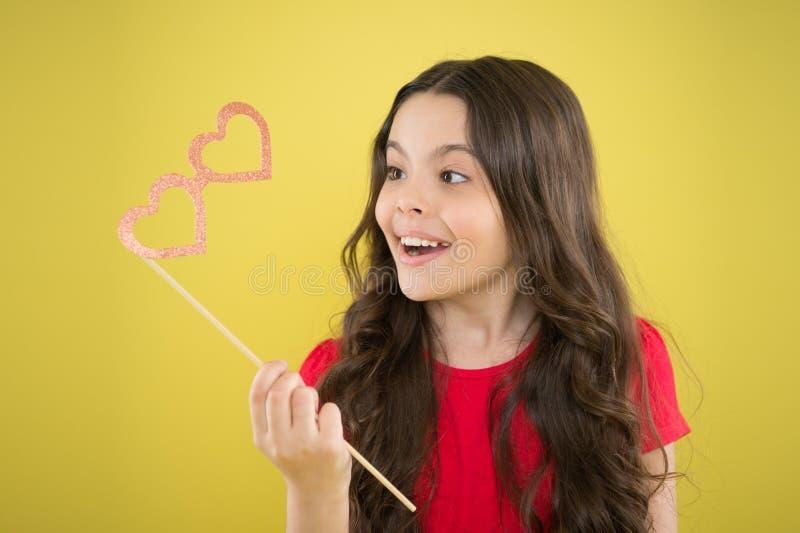 Parteigeschäft Roter heart-shaped Schmucksachegeschenkkasten und eine rote Spule auf einem Zeichen Glückliche kleines Kinderglass stockbild