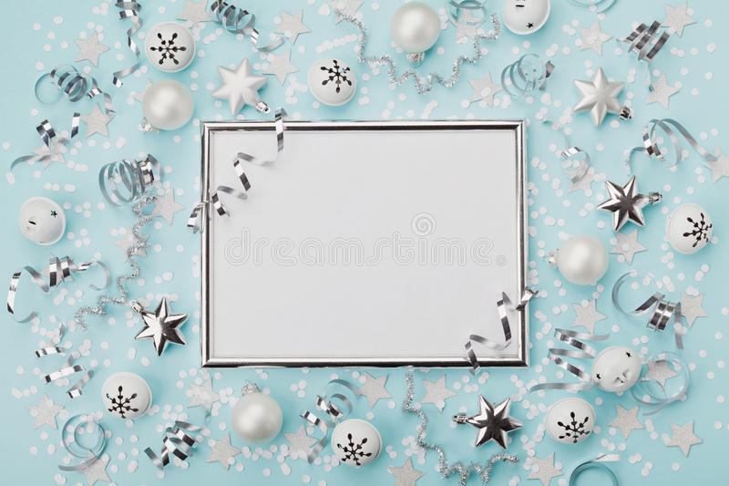 Parteikarnevals-Weihnachtshintergrund verzierter silberner Rahmen mit Konfettis, Bällen und Stern auf Türkisdesktopansicht Flache stockbild