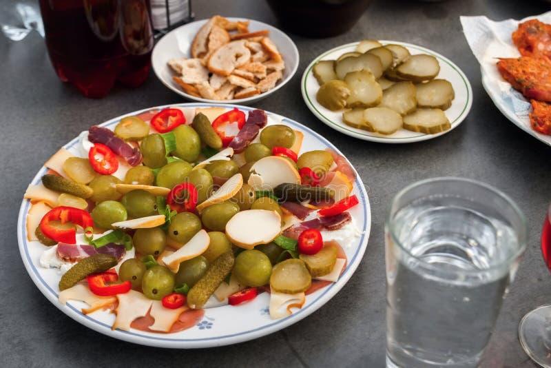 Parteiservierplatte mit Stück Käse, Traube, Gurke und Schinken, Wasser und Rebe auf Tabelle stockfotografie