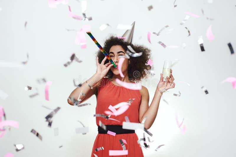 Parteizeit! Glückliche junge afroe-amerikanisch Frauen im Kleider- und Parteihut, der ein Glas mit Champagner hält und Partei dur stockbild