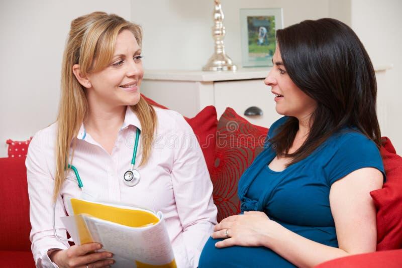Partera Discussing Medical Notes con la mujer embarazada foto de archivo