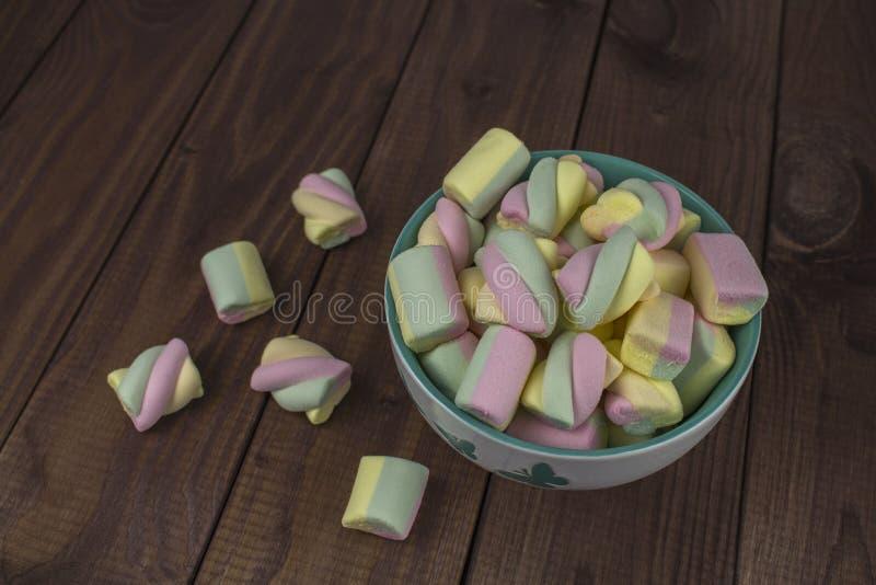 Partes coloridas de espiral do marshmallow em uma placa em uma tabela de madeira escura O arco-íris doce coloriu doces, marshmall fotos de stock royalty free