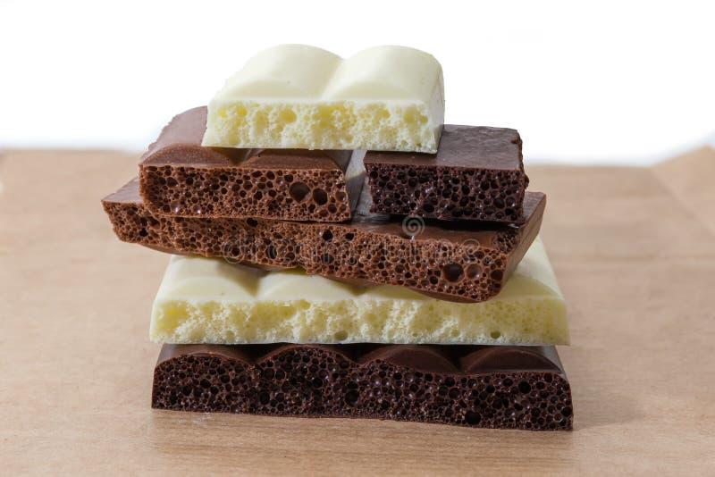 Partes da obscuridade, leite, close-up ventilado branco do chocolate imagem de stock