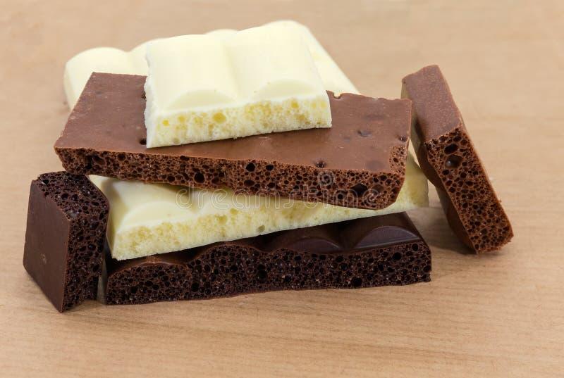 Partes da obscuridade, leite, close-up ventilado branco do chocolate imagens de stock