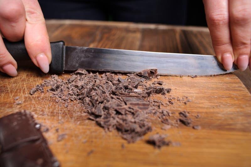 Partes de barra de chocolate escura, cubos, polvilhados com o choco raspado fotos de stock
