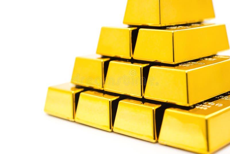 Partes de barras de ouro empilhadas acima no fundo branco imagens de stock