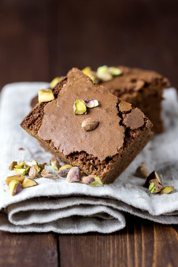 Partes de brownies caseiros do chocolate com as porcas que encontram-se no vertical do guardanapo de linho horizontal foto de stock royalty free