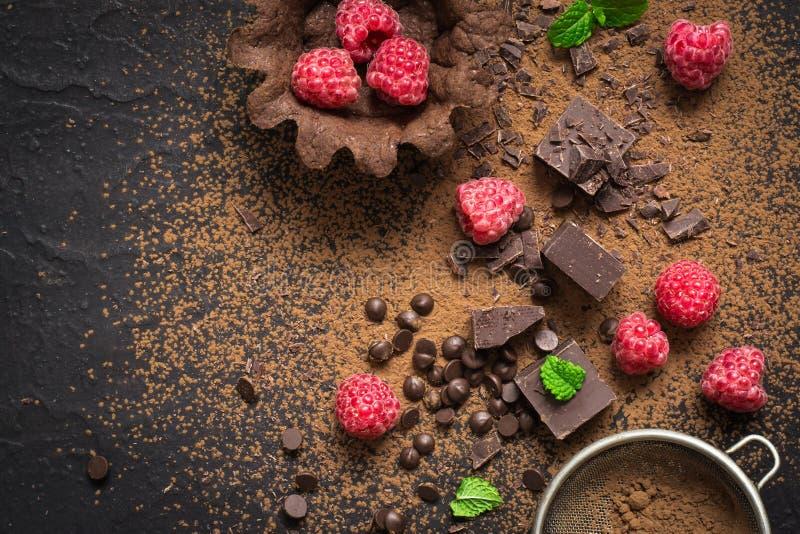 Partes de chocolate, de framboesas frescas e de tartlets preparação Fundo da sobremesa do alimento imagem de stock royalty free