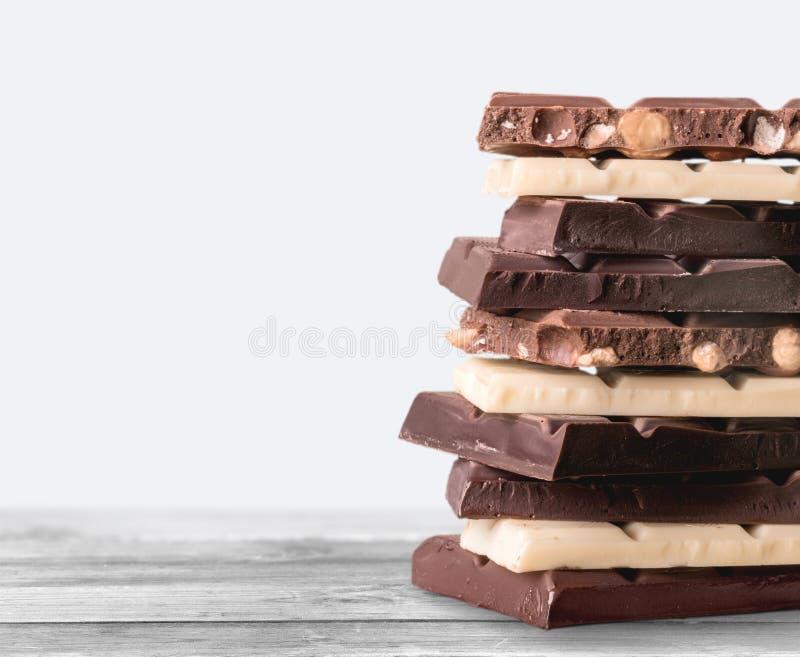 Partes de chocolate delicioso no fundo imagem de stock royalty free