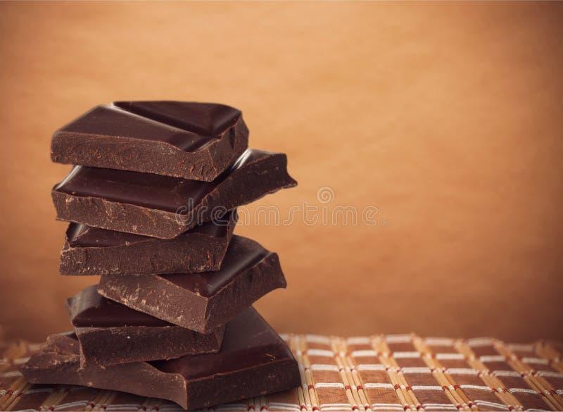 Partes de chocolate delicioso no fundo branco fotografia de stock