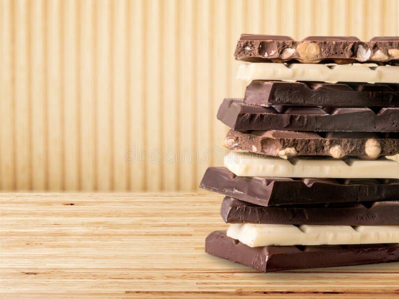 Partes de chocolate delicioso no fundo claro foto de stock royalty free