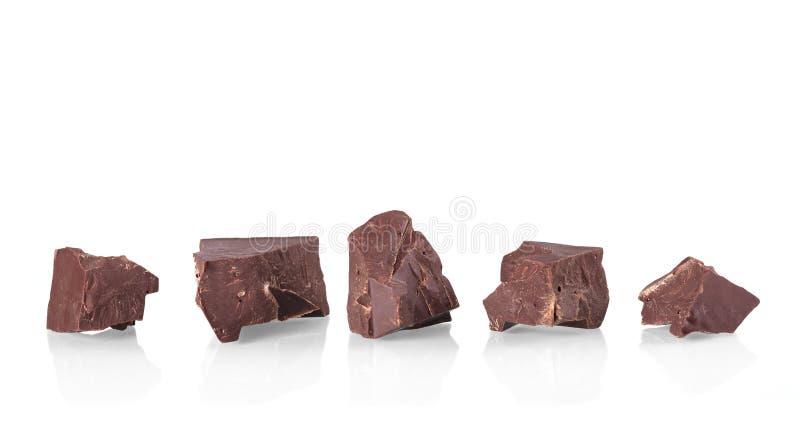 Partes de chocolate delicioso preto isolado no branco imagens de stock