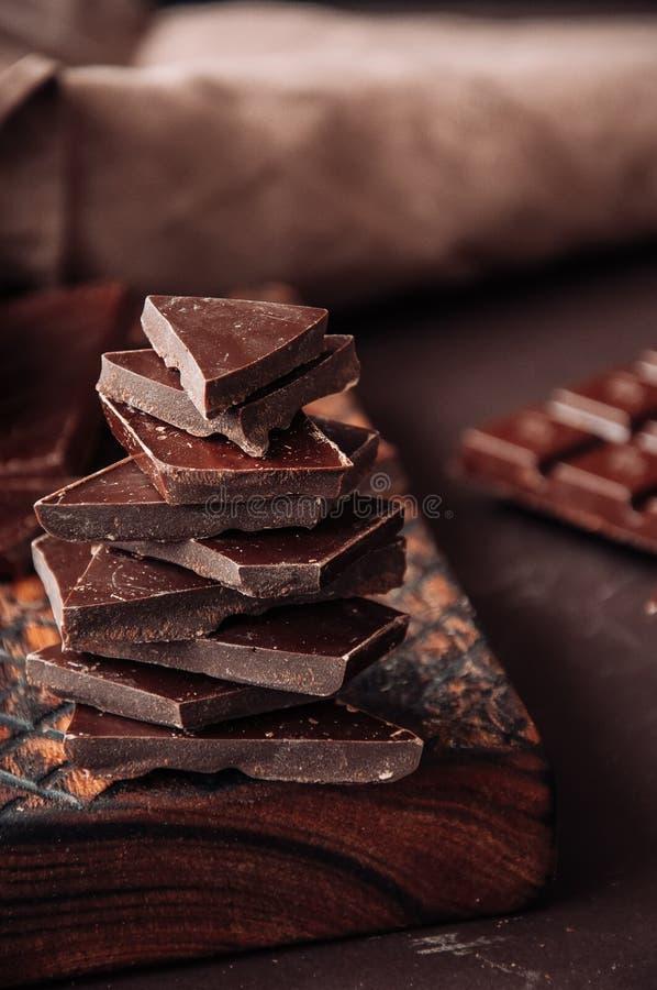 Partes de chocolate escuro em uma placa de madeira no ajuste monocromático fotos de stock
