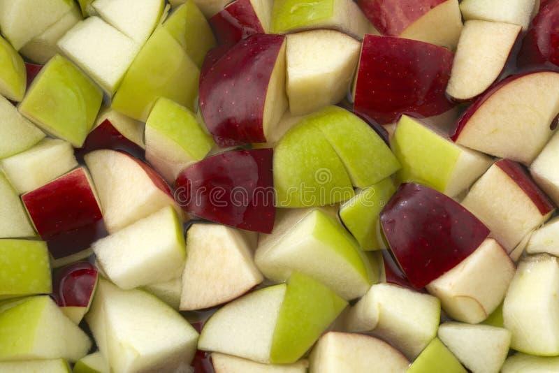 Partes de maçãs vermelhas e verdes na água imagem de stock