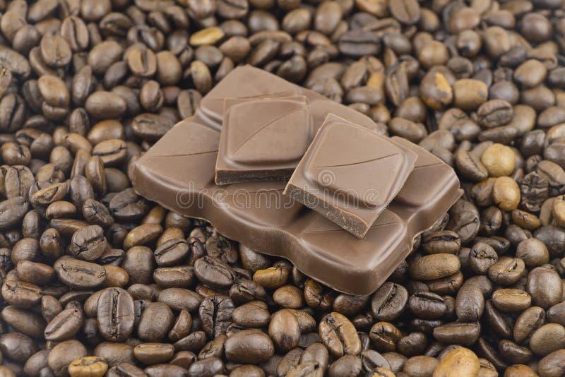 Partes de mentira do chocolate de leite entre feijões de café fotos de stock